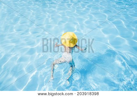 Young woman in yellow sunhat swimming at the basin with blue water. General view from above