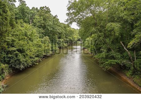 A tree lined river in the appalachian mountains.