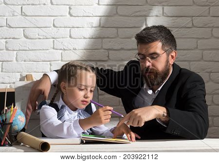 Schoolgirl and her dad with busy faces learn how to write. Classroom and home education concept. Girl and her father read book on white brick background. Family works at desk with school supplies