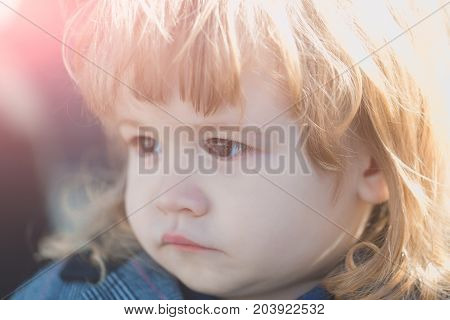 Happy childhood concept. Kid with long blond hair. Toddler boy with cute face. Baby on sunny day outdoors. Child with brown eyes.