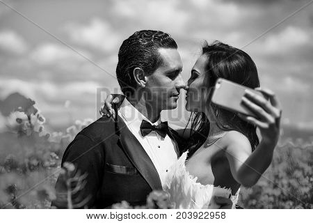 young wedding couple of sexy girl with pretty face in white bride dress holds mobile phone and handsome man in black groom suit kiss in field with yellow flowers on natural background with blue sky