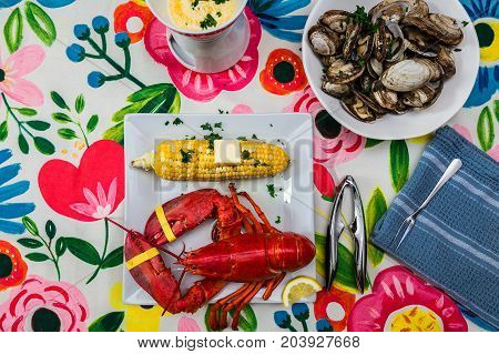 A lobster dinner with a bowl of streamer clams and corn on the cob. A dish of melted butter and a shell cracker. Set on a colorful table cloth