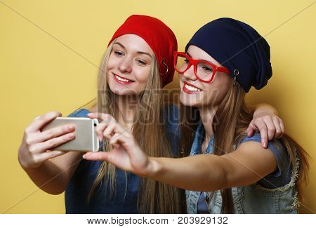 lifestyle, tehnology and people concept: Happy girls  with smartphone  over yellow background. Happy selfie.