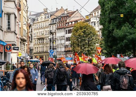 STRASBOURG FRANCE - SEPT 12 2017: Demonstrators walks on street under rain during a French Nationwide day of protest against the labor reform proposed by Emmanuel Macron Government