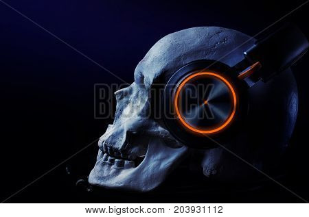 Human skull with blue-tooth headset with led highlight laying on a table on black background.