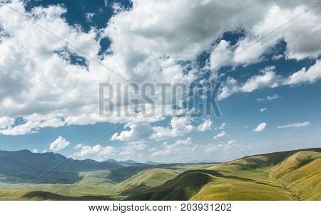 Green Hills And Mountain Range On A Sunny Summer Day. Elbrus Region North Caucasus Russia