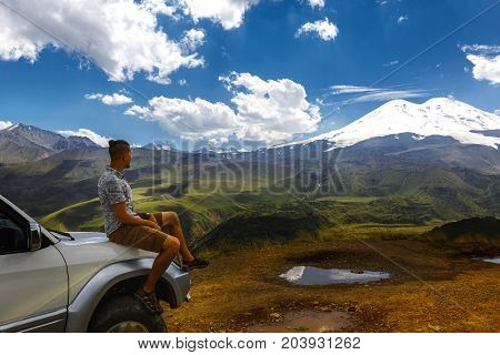 Young Traveler Man Sits On Car And Enjoys View Of Mountains In Summer. Elbrus Region North Caucasus Russia