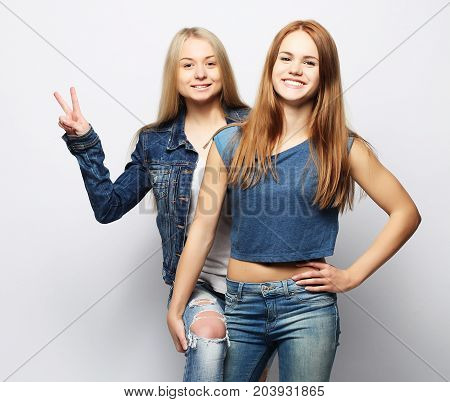 emotions, people, teens and friendship concept - two beautiful young teen girl giving victory hand sign