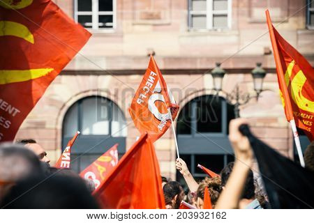 STRASBOURG FRANCE - SEPT 12 2017: Young communist movement flags at political march during a French Nationwide day of protest against the labor reform proposed by Emmanuel Macron Government
