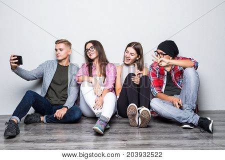 Group Of Beautiful Students In Casual Clothes Doing Selfie Using A Smartphone And Smiling While Sitt