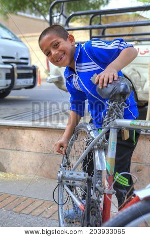 Fars Province Shiraz Iran - 18 april 2017: One unknown boy about 10 years old is repairing a bicycle on a city street.