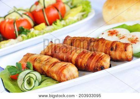 Rolled meat with bacon on the plate