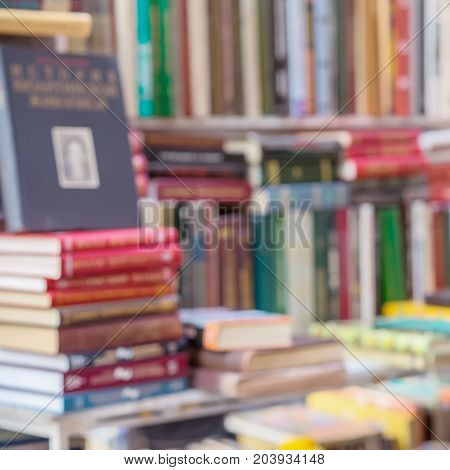 Many books, textbooks or fiction in rows lying on the table, on the shelves in library or in modern urban bookshop. Self-study, educational, manuals, textbooks, school, study concept. Blurred abstract square background