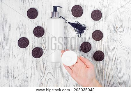 Female hand cream cotton pad cookie on a white wooden background