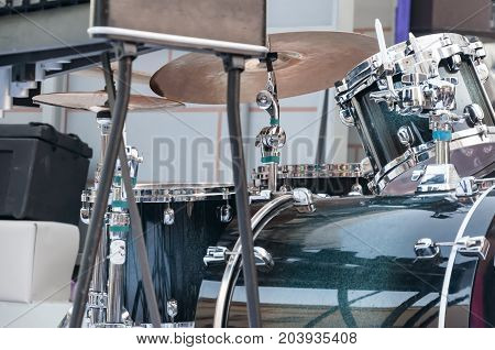 A drum set a musical instrument stands on the stage in the street.