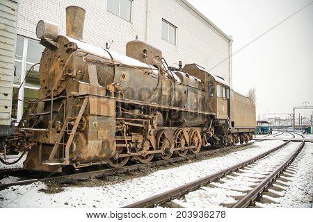 Old rusty steam locomotive on railroad in winter