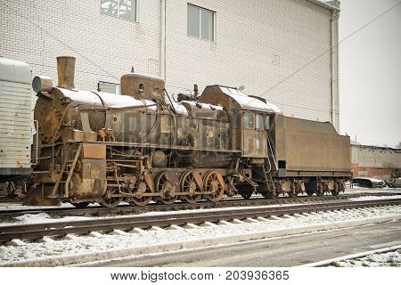 Old rusty steam engine on railroad in winter