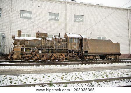 Old rusty steam train locomotive on railroad in winter