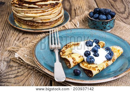 American pancakes with sauce and blueberries on wooden table top. Studio Photo