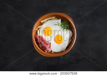 Traditional spanish lunch - fried eggs with french fries, cured pork slices of jamon on the black chalkboard