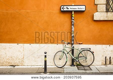 VERONA ITALY - JUNE 25 2016: A green bike chained into a Palazzo Victoria direction pole in an alley with an colorful orange wall. Verona Italy.