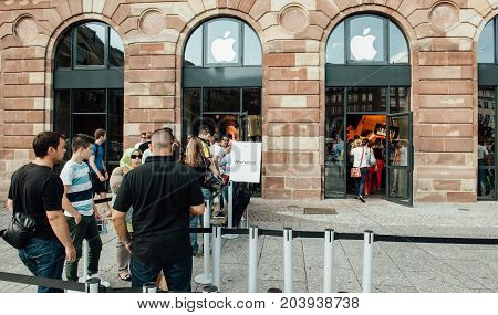 STRASBOURG FRANCE - SEP 20 2014: Customers waiting in line to pick-up their new reserved iPhone 7 from the Apple Store computer store selling iPad Apple Watch and iMac MacBook pro computers
