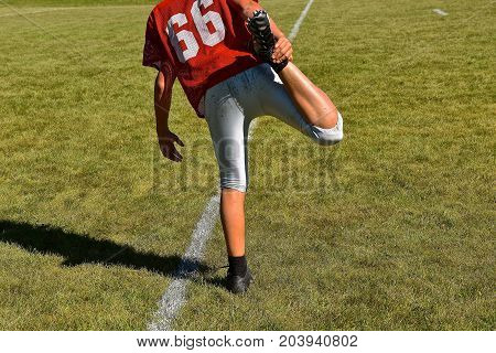 A young unidentified football player stretches leg muscles prior to practice