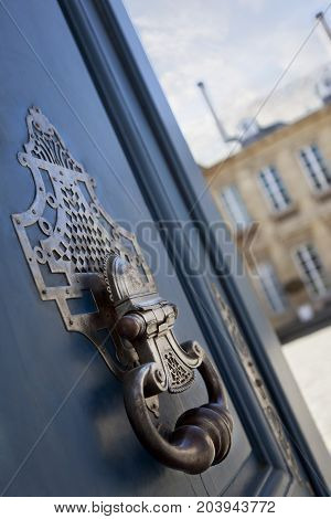 Bronze door knocker on a French mansion wooden door