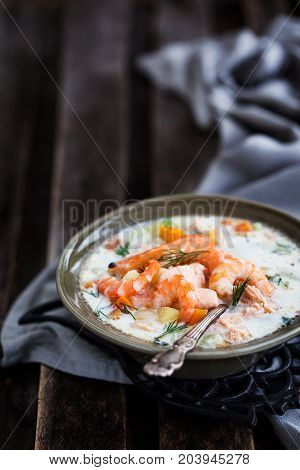 Hot salmon and shrimps cream soup on wooden table