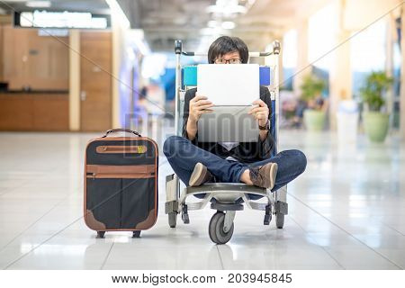 Young asian man holding laptop computer sitting on airport trolley in international airport terminal freelance lifestyle and digital nomad concepts