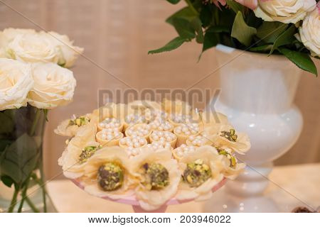 Horizontal picture of ornated table with bonbon with white chocolate and flowers for woman party
