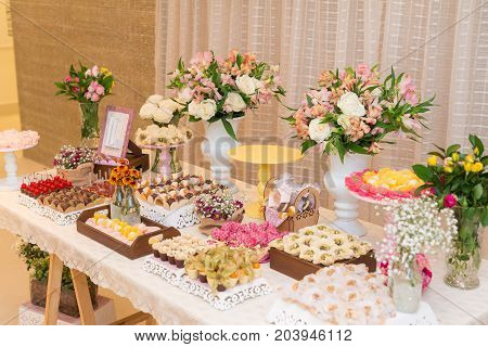SAO PAULO BRAZIL - SEPTEMBER 09 2017: Horizontal picture of ornated table with different kinds of candy chocolates truffles and flowers for woman party