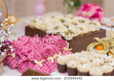 Horizontal picture of ornated table with small pink bags and bonbon with fruits for woman party