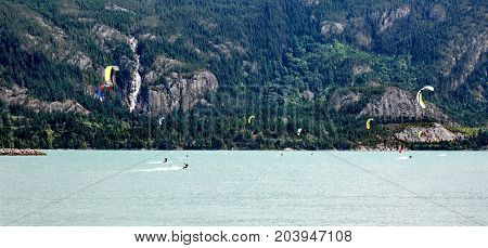 Kiteboarding. Fun in the ocean. Extreme Sport Kite surfing. Kite surfers On the background of mountain hill and Shannon Falls.