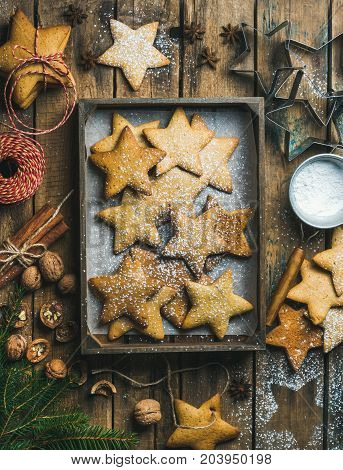 Flat-lay of gingerbread star shaped cookies in wooden tray with baking paper at bottom, sugar powder, nuts, spices, baking molds, fir-tree branch and decorative rope on wooden background, top view
