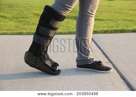 Lady walking with a cast boot on right foot