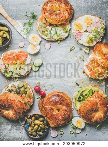 Flat-lay of bagels with salmon, eggs, radish, avocado, cucumber, greens and cream cheese for breakfast, healthy lunch or party over grey concrete background, top view, copy space. Takeaway food concept