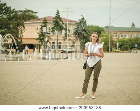 Young beautiful woman in the town square communicates through an electronic device. Portrait of woman in full growth in the city.