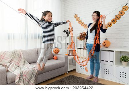Happy Mother Looks Her Cute Girl Play Fly Jump