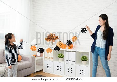 cute girl holding decorations with her mother ready to decorate the house for halloween party at home