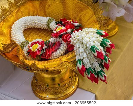 Garland or Lei of flowers on gold tray with pedestal