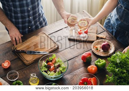 Couple cooking together delicious and healthy dinner and drinks wine on a wooden table in home kitchen
