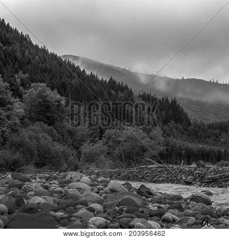 River at bottom of mount rainier in black and white with clouds in background.