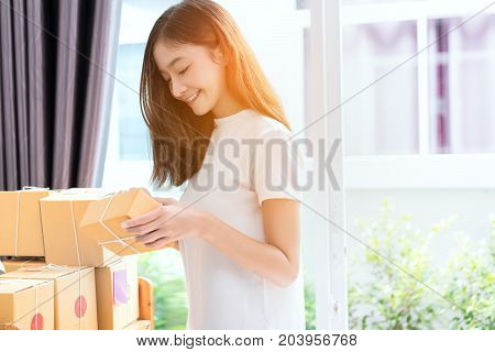 Young asian girl freelancer business owner working at home office with note post it packaging sort box delivery online market on purchase orders to customer.