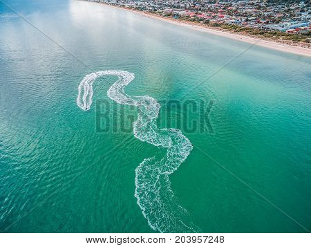 Aerial view of jet ski making zigzags in water near beach