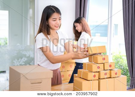 Young asian girl together freelancer business small owner working at home office with packaging sort box delivery online market on purchase orders to customer.