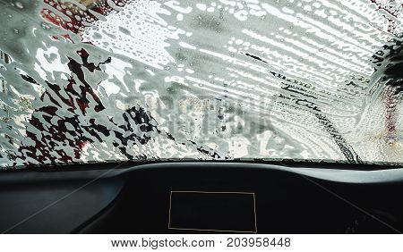 Washing windshield screen of modern car, view from inside