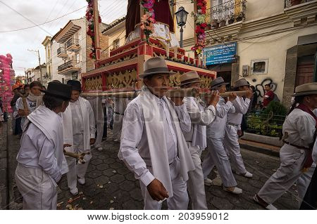 April 14, 2017 Cotacachi, Ecuador: indigenous kechwa men walking with religious float on their shoulder at Easter procession