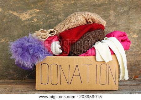 Donation box with clothes on the old wooden background..