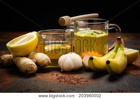 Selection of food against flu. Natural product for excellent immunity - herbal tea, lemon, ginger, honey, bananas and broth soup. Space for text